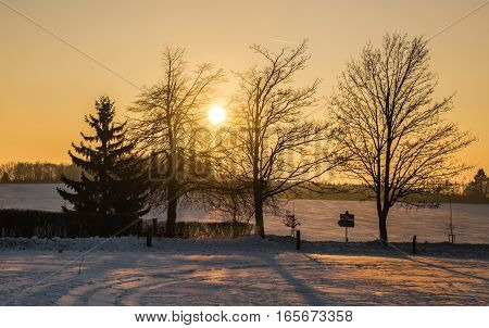 Snowy landscape and sunset through the trees. Moravian landscape Benesov.