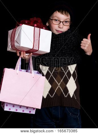 small smiling boy or cute nerd kid in glasses hat and fashionable knitted scarf on black background holds white present box with red bow and shopping bags holds thumb up