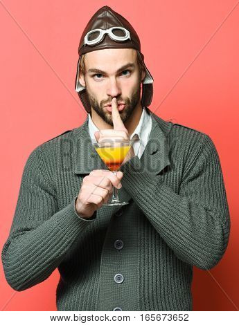 handsome bearded aviator man with long beard on serious face holding glass of alcoholic cocktail in gray knitted sweater with hat and glasses on red studio background
