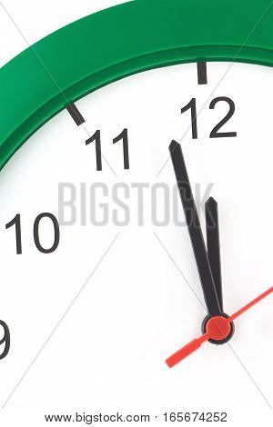 Almost twelve o'clock on big wall clock isolated on white vertical close up