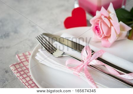 Valentines day table setting. Plate silverware flower and gift box.