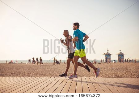 Young healthy lifestyle men running on a beach.