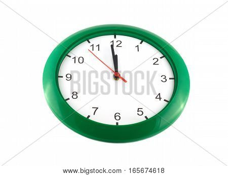 Big wall clock in green case cover shows almost twelve o'clock isolated on white close up