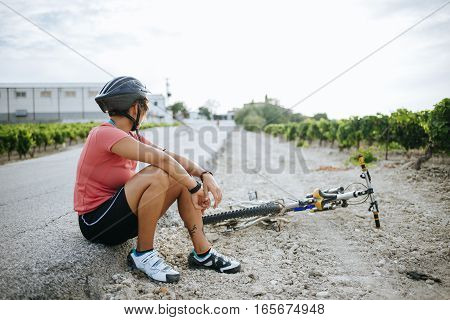 Woman cyclist sitting with her bike on the road.