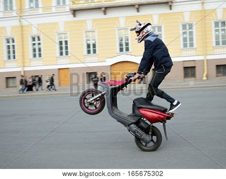 Reckless driver on the scooter performs complex and dangerous stunt.