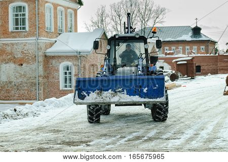 Priirtyshsky, Russia - May 2, 2010: Tractor with snowplowing equipment cleans road in Ioanno-Vvedensky female monastery. Tobolsk district
