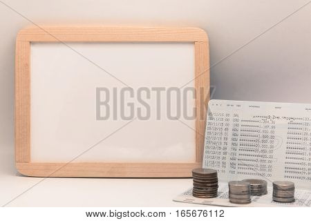 Blank whiteboard with calculator. Passbook blank paper and coins on white table for mocup display planning Money Financial Accounting Concept