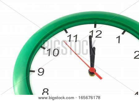 Fragment of big wall clock with green case shows almost twelve o'clock isolated on white close up
