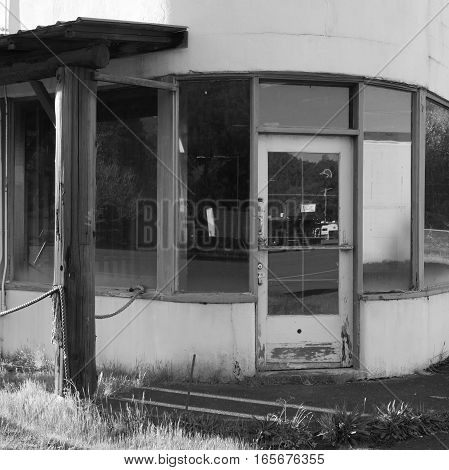 An old and abandoned building rounded on the corner with a door and several windows in the small town of Oakridge in Lane County in Western Oregon on a spring day.