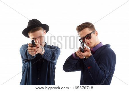 Two young well dressed men aiming guns