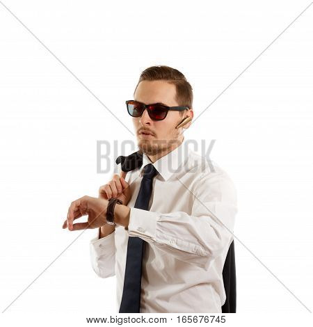 Businessman with sunglasses checking his wristwatch on white background