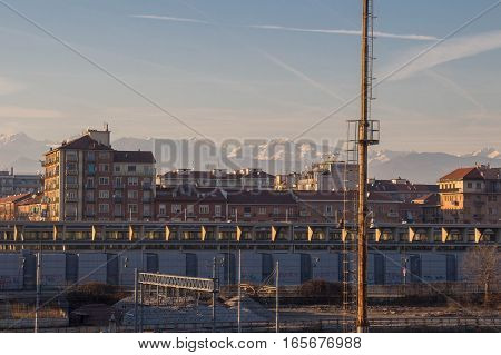 Italy Turin - January 5 2015: view of railway typical buildings and white mountains on background on January 05 2015 in Turin Italy.