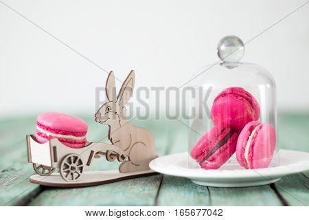 Colorful macaroon with toy rabbit on wooden background. Easter concept