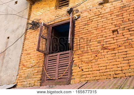 Open wooden window on a brick wall of a building Nepal.