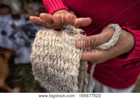 closeup of a womans hand presenting a woven strap made from natural fibres of a local cactus