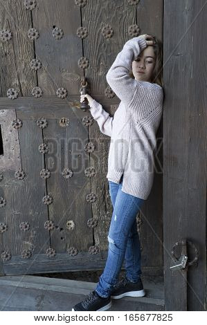 Girl Next To An Old Wooden Door.