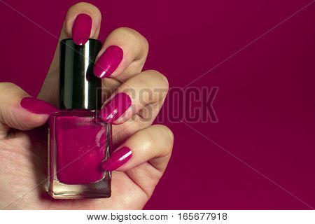 Female hand with pink nails holds pink nail polish on pink background.