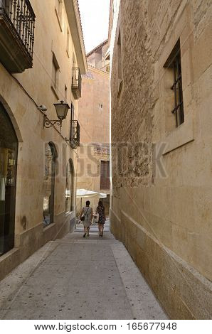 SALAMANCA, SPAIN - AUGUST 3, 2016: Two women walking by a narrow street in the historical part of the city of Salamanca Spain.