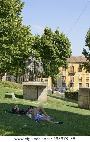SALAMANCA, SPAIN - AUGUST 3, 2016: Couple resting on grass next to an urban sculpture dedicated to Lazarillo character of an Spanish novella in Salamanca Spain.