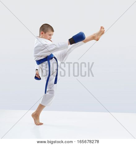 High kick forward karateka is beating in karategi