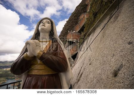 November 8, 2016 Guatape, Colombia: a religious statue is mounted on the side of the monolith of Penol at half distance between the bottom and the top