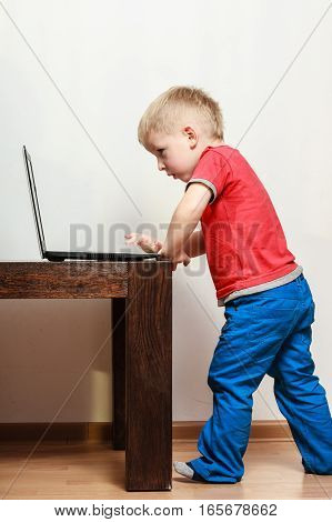 Technology and early education. Child use laptop for fun and learning. Boy stand alone with computer on table wear red shirt and blue trousers.