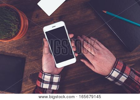Casual female graphic designer using smart phone top view of office desktop