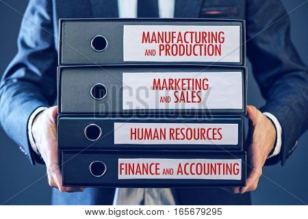 Businessman holding document binders with four major business functions - manufacturing production marketing sales human resources finance accounting