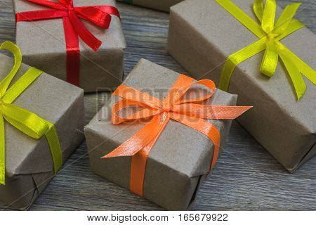 Gift Box With Paper Wrapper With Coloured Strips On The Old Wooden Table