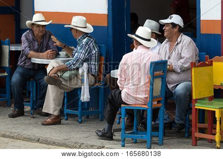 September 30, 2016 El Jardin, Colombia: men sitting on coffee house patio in the centre of the small colonial town