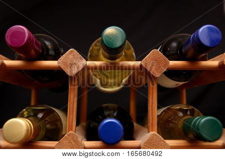 Low Angle Shot Of Bottles In A Wooden Wine Rack On Dark Background