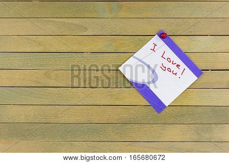 By the wooden surface is attached pushpin leaf with the words