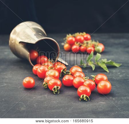Organic cherry tomatoes in vintage silver milk jug on slate close-up selective focus. Retro styled food background.