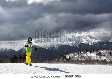 Young skier with ski poles in sun mountains and cloudy gray sky before blizzard. Caucasus Mountains. Hatsvali Svaneti region of Georgia.