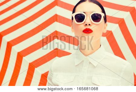 Fashion portrait of a beautiful woman wearing white chemise and sunglasses with bright painted lips next to a striped background