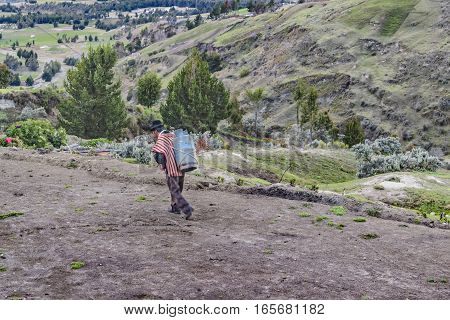 QUILOTOA, ECUADOR, FEBRAURY - 2016 - Andean worker carrying a bag while walking to dirty path at border of Quilotoa crater Latacunga Ecuador
