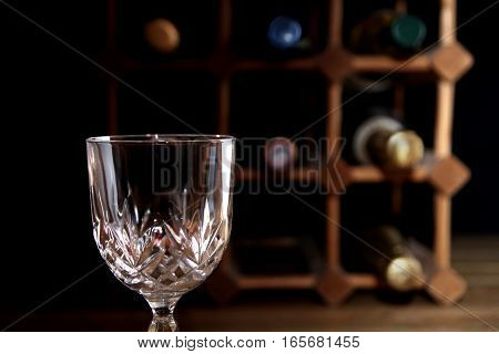 Empty Wine Glass With Wooden Wine Rack In Blurred Background