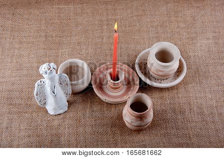 Greybeard candlestick with pattern red burning candle and white angel made of clay lay on brown sackcloth background
