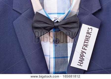 Father's greeting paper on suit. Checkered shirt with bow tie. Fashionable formal menswear.