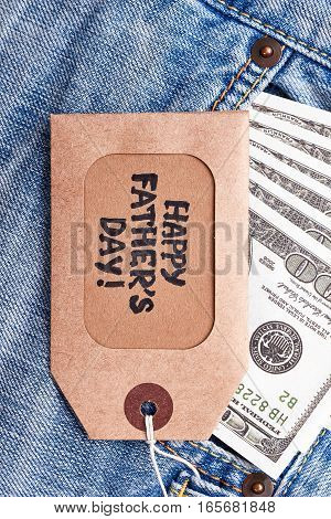 Father's Day label near money. Greeting tag, dollars, jeans. Nice and also useful gift.