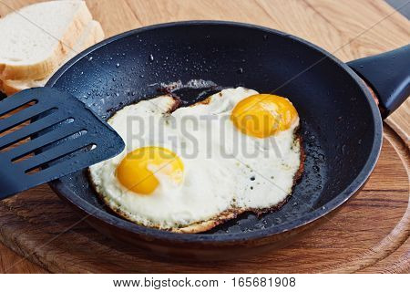 Fried eggs in a frying pan on a table on a wooden stand