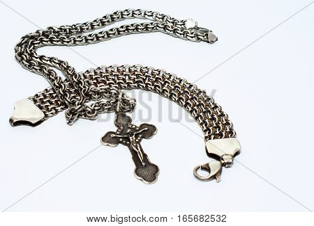 Bracelets chains and crosses of silver on a white background