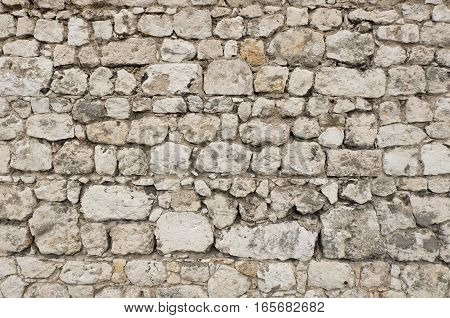 Stone wall of a ancient fortress or antique castle made of white and gray colored stone blocks with irregular structure.