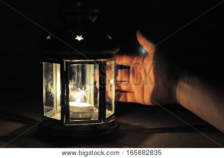 Hand illuminated with light from candle lantern in dark black background with soft fire