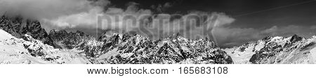 Black And White Large Panoramic View On Snow Mountains In Haze At Sunny Day
