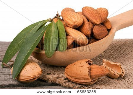 heap of peeled almonds with leaf on a wooden table isolated on white background.