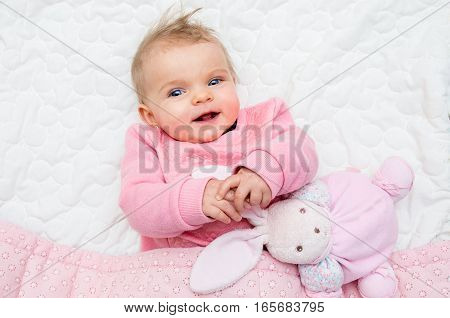 Happy Infant Baby Girl Smiling On Bed With His Toy Bunny