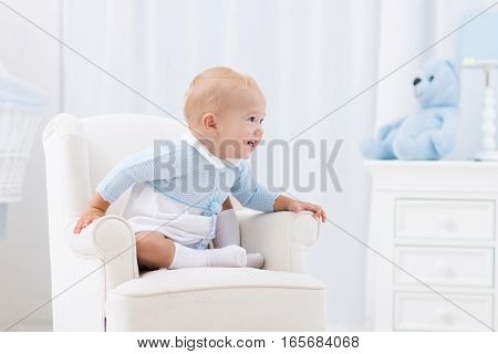 Adorable baby boy playing in white sunny bedroom. Happy child relaxing in toy chair on play mat. Nursery and play room for young children. Infant furniture clothing textile and bedding for kids.