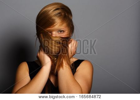Beautiful young woman hiding her face under the long blonde hair on grey background