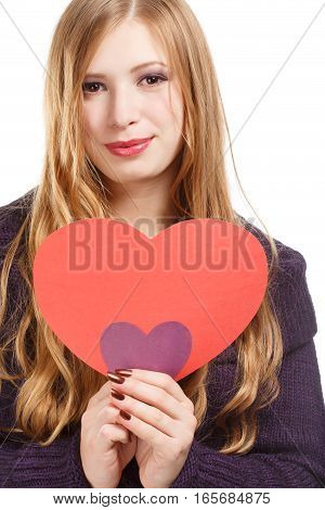 Young beautiful smiling woman with long blonde hair in dark purple pullover with red and violet paper hearts in hands isolated on white background.